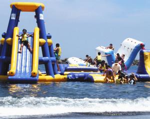 海上に設置された滑り台やシーソーを楽しむ子どもたち=伊東市のオレンジビーチで