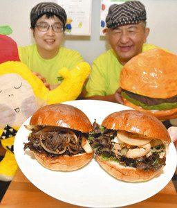 カフェで販売するジンギスバーガーととりじんバーガーをPRする榊山さん(右)と早川さん=飯田市中央通りで