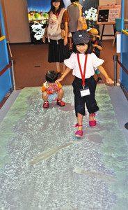 床に映し出された矢勝川の魚を追い掛けて遊ぶ子どもたち=半田市中村町のミツカンミュージアムで
