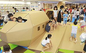 段ボールでできた飛行機の遊具で楽しむ子どもたち=名古屋市千種区の名古屋三越星ケ丘店で