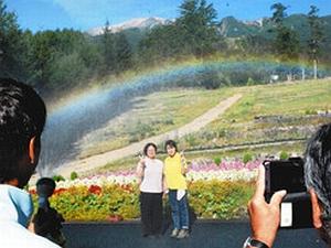 御嶽山を背景に散水して作る虹と利用客を撮影するサービス「いってらっしゃいレインボー」=4日、木曽町の御岳ロープウェイで(中央の被撮影者はスタッフ)