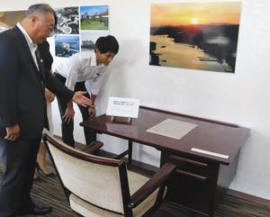 志摩観光ホテルで山崎さんが使った机といす。置かれているのは華麗なる一族の原稿のレプリカ((c)一般社団法人山崎豊子著作権管理法人)=志摩市阿児町のサミエールで