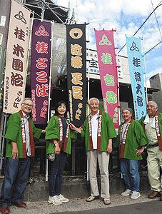 上方落語の会に向け、出演者ののぼり旗を掲げる近藤さん(中)ら=郡上市八幡町で
