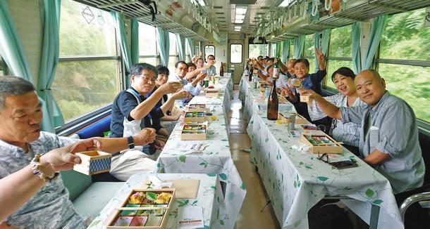 「枡酒列車」で乾杯する人たち=恵那市内で