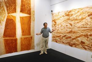 鉄さびを布に写し取った作品を解説する長谷さん=若狭町熊川の熊川宿若狭美術館で