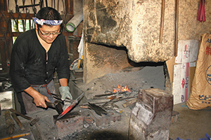 汗をかきながら包丁作りに取り組む広瀬さん=いずれも愛知県豊田市足助町の三州足助屋敷で