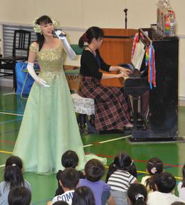 児童の前で被爆したピアノの伴奏で歌うまほろば遊さん(左)=名古屋市名東区の貴船小で
