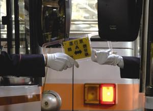 トロリーバスの運転手が、対向するバスの運転手に運行票を渡す様子