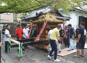 神輿を蔵から出し、傷をつけないように注意深く舞殿に移す氏子ら=大津市京町の天孫神社で