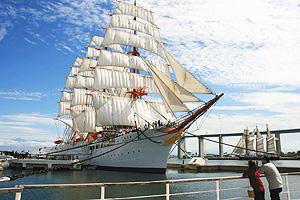 立山連峰や新湊大橋をバックに帆を広げて今にも動きだしそうな海王丸=富山県射水市で
