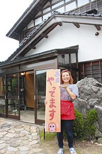 民家を改装して開店した「ごはん家ござる」。開店の看板を掲げる渡辺有美子さん=宝達志水町森本で