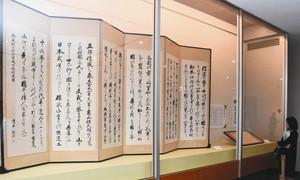 「信濃の国」の歌詞をつづった浅井直筆のびょうぶ(左)などが並ぶ会場=松本市丸の内の市立博物館で