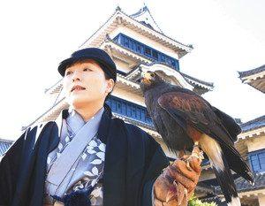 11月のイベントをPRする大塚さんとハリスホーク=松本市丸の内の松本城本丸庭園で