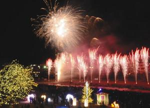イルミネーションを前に、音楽に合わせて打ち上げられる花火=下呂市の飛騨川河川敷で
