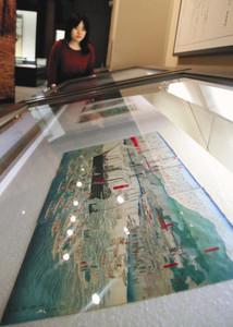 武四郎が生きた時代を映す錦絵が並ぶ。手前は「現如上人北海道開拓巡教錦絵」=松阪市の武四郎記念館で