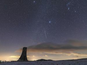 ふたご座流星群の極大を迎え、夜空を駆ける流れ星。手前左は美しの塔(20秒露光)=15日午前1時20分、上田市・長和町境の美ケ原高原で