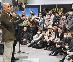 多くの来場者を前に撮影の裏話を披露する岩合さん(左端)=長野市
