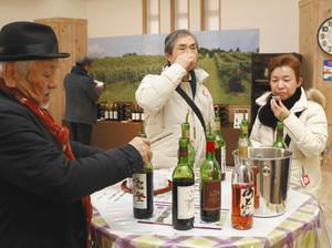 能登ワインの商品を試飲する首都圏からのツアー客ら=穴水町旭ケ丘で