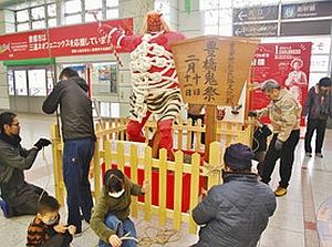 改札前で赤鬼の人形を設置する鬼祭り関係者=豊橋駅で