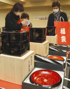 慎重な手つきで輪島塗の商品を福袋に詰める実行委員会のメンバーたち=輪島市文化会館で