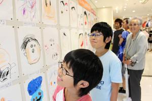 展示された似顔絵を見つめる家族客たち=津市東丸之内の津松菱で