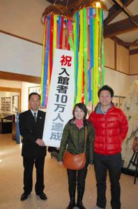 川上館長(左)と10万人達成を喜ぶ浅井さん(右)と戎さん=下呂市湯之島の下呂発温泉博物館で