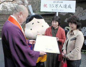 鷲尾遍隆座主(左)から来場15万人目の記念品を受ける根来洋子さん(右)と井山孝子さん=大津市石山寺で