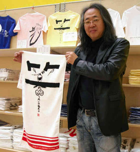 即売コーナーでスヌーピー作品をあしらったタオルを持つ大谷さん
