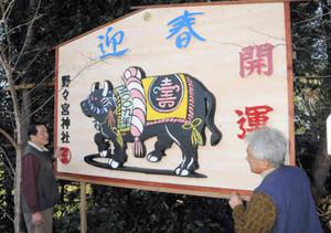 神社境内に大絵馬を飾った迫間さん(左)=東近江市の野々宮神社で