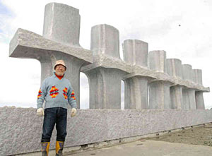 台座の上に本設置された彫刻作品と大成さん=魚津市の海の駅「蜃気楼」前で