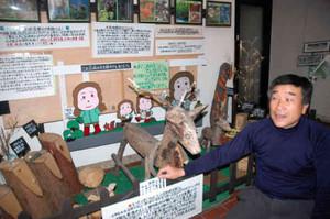 「森は地球を救う」。手作りした展示コーナーと山口明男さん=安曇野市三郷総合支所で