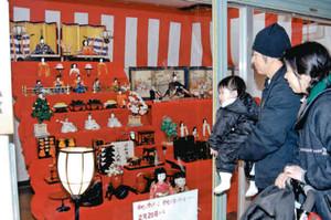 商店街に飾られたひな人形を眺める親子=伊賀市上野東町で
