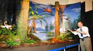 花咲く植物が現れたばかりの森のジオラマを紹介する孫革所長=勝山市の県立恐竜博物館で