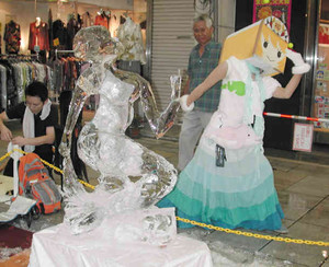 お目見えした人魚の氷像に合わせてポーズを決める「やなな」。7、8両日はゆっくりとやななと過ごせる=岐阜市柳ケ瀬で