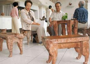 愛猫の姿をモチーフにしたいすなどを展示している林さん(右から2人目)=南木曽町のホテル木曽路で