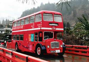 中橋など古い町並みを通り、飛騨高山美術館へ向かうロンドンバス=高山市の中橋で