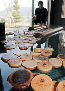 湯船に浮かべられた尾鷲ヒノキと日光杉の入浴木=尾鷲市向井の夢古道の湯で