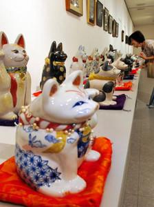 岐阜県の陶磁器デザイナーが作った表情豊かな招き猫が並ぶ会場=名古屋市西区のノリタケの森ギャラリーで
