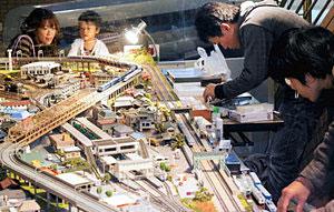 クラブ員が整備する鉄道模型のジオラマを楽しむ親子=白山市西新町で