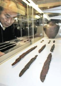 深山寺経塚から出土し、展示されている刀剣。奥は常滑焼のかめ=敦賀市相生町の市立博物館