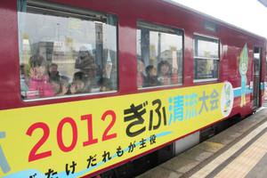 「ミナモ列車」に乗って窓越しから手を振る子どもたち=長良川鉄道関駅で