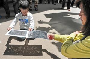 ピンホール投影板を使って太陽を観察する親子=大野市の県自然保護センターで