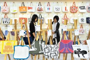 個性的な模様が描かれた「印染トートバッグ」が並ぶ会場=名古屋市中村区のトライデントデザイン専門学校で