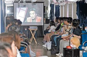 恐ろしい雰囲気が演出された車内で、稲川淳二さんの怪談DVDを見る乗客ら=福井市内で