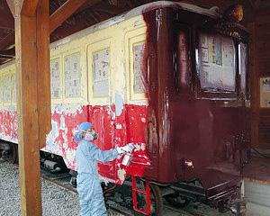 キハ3の塗り替えをする会員=小松市ポッポ汽車展示館で