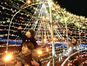 歓声を上げながら電飾のアーチをくぐる人たち=紀宝町の田代公園で