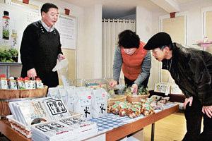 生産者(左)から農産品の説明を聞く客ら=金沢市安江町で
