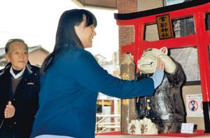 「合格祈願招き猫」を作った松下さん(左)らの前で、肉球の「触り初め」をする沢田さん=常滑市鯉江本町の名鉄常滑駅で
