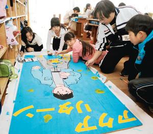 校舎や上映会場に掲げる看板の制作を進める児童と麻和教諭(右から2人目)=松本市の開智小で