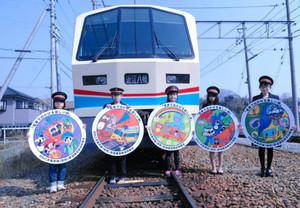 表彰された小学生と電車ヘッドマークデザイン=東近江市の近江鉄道八日市駅で